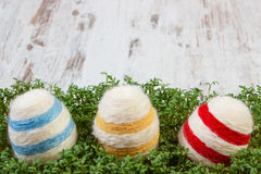 Easter eggs wrapped woolen string and green cress on wooden background, copy space for text, decoration for Easter Royalty Free Stock Photos