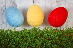 Easter eggs wrapped woolen string and green cress on wooden background, decoration for Easter Royalty Free Stock Photography
