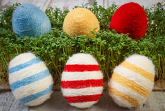 Easter eggs wrapped woolen string and green cress on wooden background, decoration for Easter Stock Photography