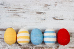Easter eggs wrapped woolen string on wooden background, copy space for text, decoration for Easter Stock Image