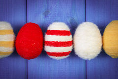Easter eggs wrapped woolen string on wooden boards, decoration for Easter Stock Photos