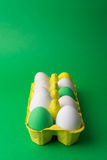Easter eggs in yellow carton on green background. Colorful Easter eggs in yellow carton on green background. Easter holiday painted eggs in a box. Copy space Stock Photo