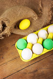 Easter eggs in yellow carton with jute decor. Closeup of white, yellow and green Easter eggs in yellow carton with jute decor on wooden surface Royalty Free Stock Image