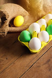 Easter eggs in yellow carton with jute decoration. Closeup of colorful Easter eggs in yellow carton with jute decoration on wooden surface. Easter holiday Stock Photo