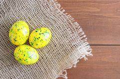 Easter eggs of yellow color green splashes. On linen fabric brown. Wooden brown background stock photos