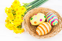 Easter eggs with yellow daffodils Stock Photo