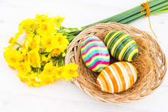 Easter eggs with yellow daffodils Stock Photography