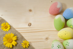 Easter eggs, yellow daisies. On natural wood Stock Photos