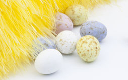Easter eggs and yellow feathers on white background. Easter eggs placed near yellow decorative fluff on white background Royalty Free Stock Photos