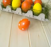 Easter. Easter eggs are yellow and orange. Eggs lie in the container for eggs. Green grass. Wooden background. Style eco. Rustic decor Royalty Free Stock Photos
