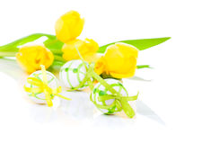 Easter eggs with yellow tulip flowers Royalty Free Stock Photos