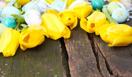 Easter eggs and yellow tulips Royalty Free Stock Image