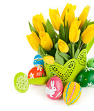 Easter eggs with yellow tulips in watering can Stock Image