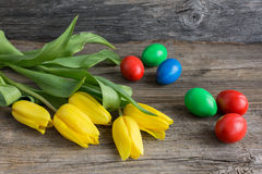 Easter eggs and yellow tulips Stock Images