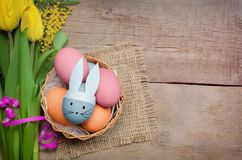 Easter eggs and yellow tulips on wooden background.  Royalty Free Stock Photos