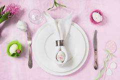Easter elegance table setting with pink flowers on pink tablecloth. Top view. Dinner. Easter elegance table setting with spring pink flowers on pink tablecloth stock image