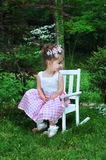 Easter Enjoyment. Sweet little girl enjoys Easter springtime dressed in her Sunday best. She is wearing a curly ribbon hairbow and a pink and white gingham dress royalty free stock photo