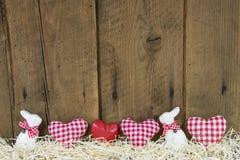 Easter för landsstil träbakgrund med röda kontrollerade hjärtor. Arkivbilder