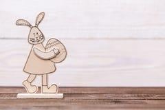 Easter feliz! Coelho de madeira em um fundo de madeira Fundo conceptual da Páscoa fotografia de stock royalty free