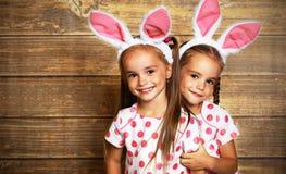 Easter feliz! irmãs bonitos das meninas dos gêmeos vestidas como coelhos no wo Foto de Stock Royalty Free