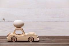 Easter feliz! O carro retro do brinquedo de madeira leva ovos em um fundo de madeira Fundo conceptual da Páscoa foto de stock royalty free