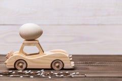 Easter feliz! O carro retro do brinquedo de madeira leva ovos em um fundo de madeira Fundo conceptual da Páscoa fotos de stock
