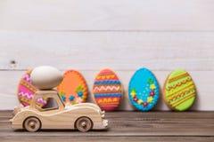 Easter feliz! O carro retro do brinquedo de madeira leva ovos em um fundo de madeira Fundo conceptual da Páscoa imagens de stock
