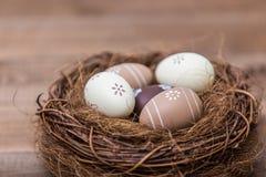 Easter feliz! Os ovos da páscoa bonitos são decorados em cores da cama em um ninho em um fundo de madeira Páscoa conceptual imagens de stock royalty free
