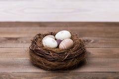 Easter feliz! Os ovos da páscoa bonitos são decorados em cores da cama em um ninho em um fundo de madeira Páscoa conceptual fotografia de stock