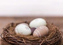 Easter feliz! Os ovos da páscoa bonitos são decorados em cores da cama em um ninho em um fundo de madeira Páscoa conceptual foto de stock