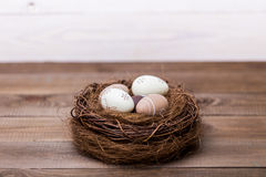 Easter feliz! Os ovos da páscoa bonitos são decorados em cores da cama em um ninho em um fundo de madeira Páscoa conceptual fotografia de stock royalty free