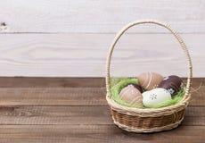 Easter feliz! Os ovos da páscoa bonitos são decorados em cores da cama em uma cesta em um fundo de madeira Páscoa conceptual imagem de stock
