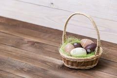 Easter feliz! Os ovos da páscoa bonitos são decorados em cores da cama em uma cesta em um fundo de madeira Páscoa conceptual foto de stock