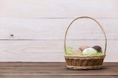 Easter feliz! Os ovos da páscoa bonitos são decorados em cores da cama em uma cesta em um fundo de madeira Páscoa conceptual fotos de stock royalty free