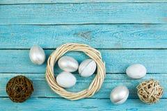Easter feliz Ovos no fundo de madeira da tabela Bolas, grinalda tecida das videiras Copie o espaço para o texto Vista superior Fotografia de Stock Royalty Free