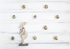 Easter festive background, quail eggs in a pattern and a wooden rabbit on white vintage wooden table. Flat lay Royalty Free Stock Images