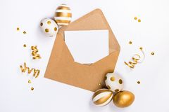 Easter festive decoration. Top view of easter eggs colored with golden paint in differen patterns and empty mock-up card in a kraf Royalty Free Stock Photos