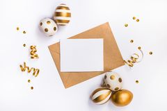 Easter festive decoration. Top view of easter eggs colored with golden paint in differen patterns and empty mock-up card in a kraf Stock Images