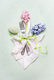 Easter festive table place setting with flowers , decor egg and cutlery on light background. Top view Stock Photography