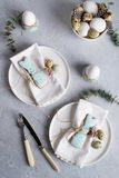 Easter  festive table setting with Easter bunny cookies, quail eggs  and chicken egg, green  leaf sprigs of eucalyptus. On a gray. Concrete background. Holiday Royalty Free Stock Photo