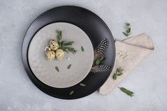 Easter  festive table setting with  gray plate, quail eggs leaf sprigs of eucalyptus. On a gray concrete background Stock Photos