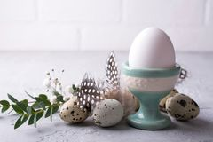 Easter  festive table setting with  quail eggs  and chicken egg standing in the egg cup with leaf sprigs of eucalyptus. On a gray concrete background Royalty Free Stock Images