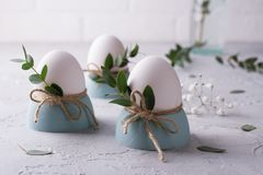 Easter  festive table setting with white chicken  eggs in eggs cups, leaf sprigs of eucalyptus. On a gray concrete background Stock Image