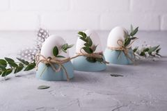 Easter  festive table setting with white chicken  eggs in eggs cups, leaf sprigs of eucalyptus. On a gray concrete background Royalty Free Stock Images