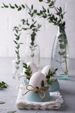 Easter  festive table setting with white chicken  eggs in eggs cups, leaf sprigs of eucalyptus. On a gray concrete background Stock Images