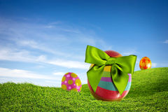 Easter Fields. Three colorful Easter eggs with green bow on a grass field