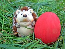 Easter figurine with red egg. Easter furry figurine on grass with red egg Stock Photography