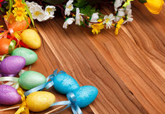 Easter flower arrangement and colorful eggs on wooden surface Stock Photo