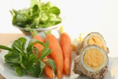 Easter food. Easter lunch or dinner recipe idea, cooked egg in a roll of veal meat, served with cooked carrots, potato and fresh corn salad stock photo