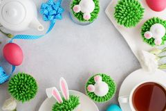 Easter background with bunny cupcakes, tea and painted eggs royalty free stock images